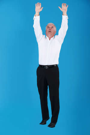 grey haired: Grey haired businessman reaching into the air Stock Photo