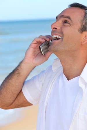 Mature man laughing into his cellphone photo
