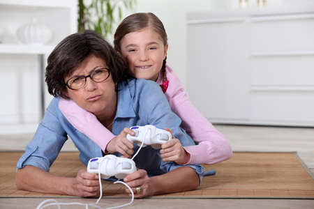 Young girl playing a video game with her grandmother photo
