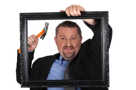 attach: El hombre a punto de clavar un cuadro en una pared Foto de archivo