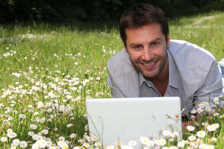 ser humano: Hombre que trabaja en la computadora portátil en las margaritas Foto de archivo