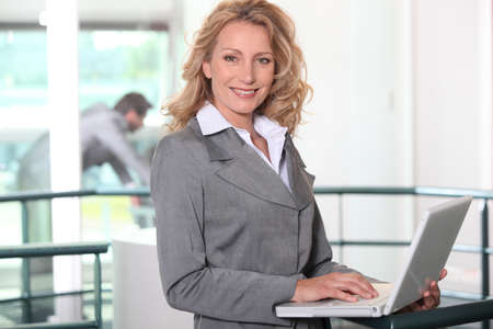 all smiles: blonde businesswoman all smiles with laptop