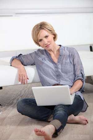 woman sitting bare-footed on the floor with laptop Stock Photo - 12638075