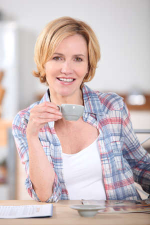 Woman having cup of coffee at kitchen table photo