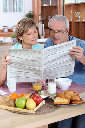 Couple reading the newspaper over breakfast photo