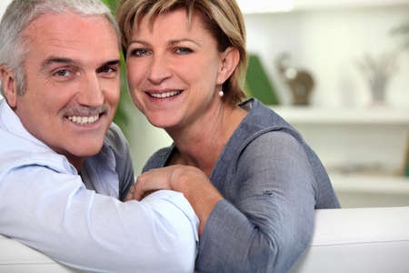 Smiling couple sitting on a sofa photo