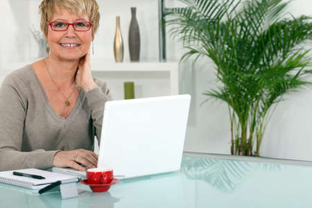 Woman working on her laptop at home photo