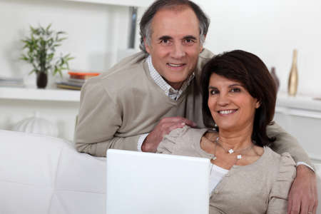 Middle-aged couple with laptop photo