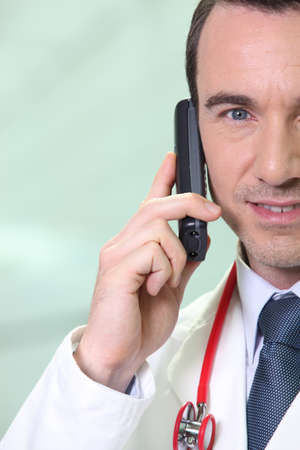 Male doctor making telephone call photo