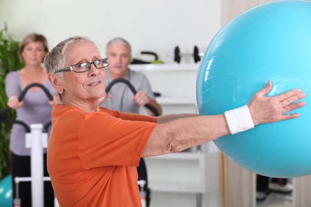 therapy group: Senior woman lifting fitness balloon