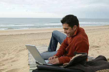 Man using his laptop at the beach photo