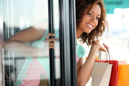 Woman leaving a store with shopping bags photo
