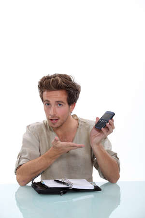 Young man with a personal organizer and cellphone Stock Photo - 12761865