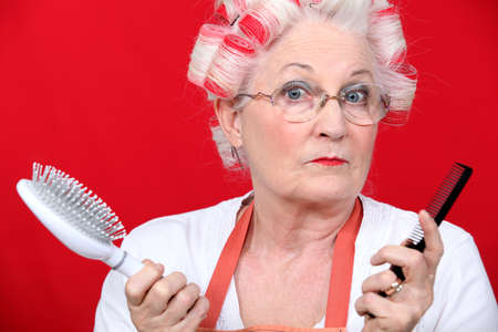 hair salon background: Senior woman with hair curlers Stock Photo
