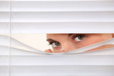 a blind: Woman peering through blinds