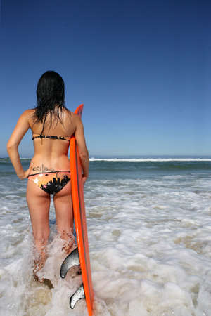 Woman stood on beach with surfboard photo