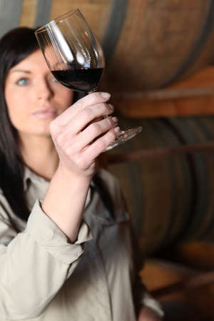 savour: a woman analyzing characteristics of a red wine glass Stock Photo
