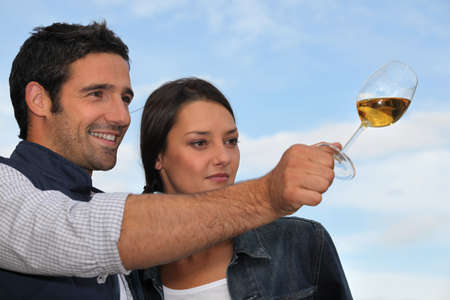 Couple tasting wine outdoors photo