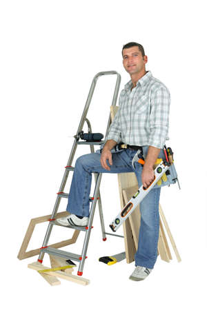 Carpenter stood with ladder and spirit-level photo