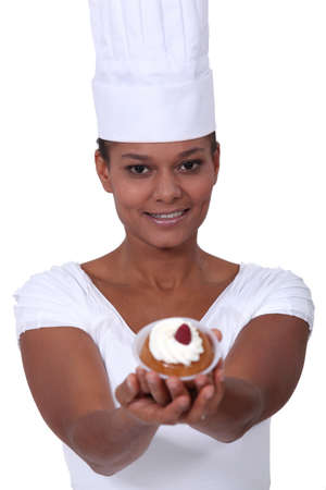 Young female baker holding pastry photo