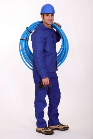 flexi: Plumber with a reel of blue pipe Stock Photo