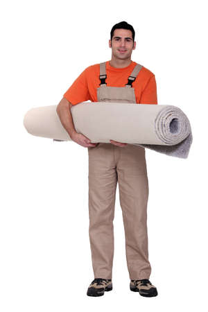 fitter: Carpet fitter carrying a roll of carpet