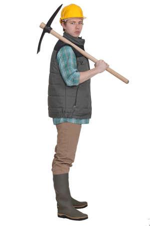 pickaxe: young bricklayer posing with pickaxe