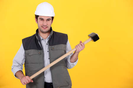 wage earner: craftsman with hammer against yellow background