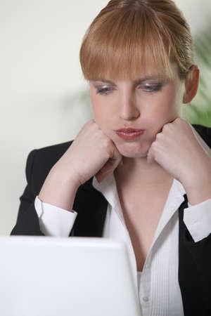 molesto: La mujer exasperada con su computadora portátil Foto de archivo