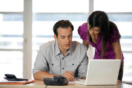Couple at a desk with a laptop photo