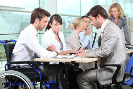 personas discapacitadas: Hombre en silla de ruedas con sus colegas en una reunión Foto de archivo