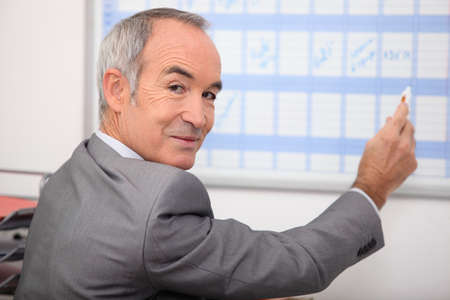 grey haired: Grey haired man writing on calendar