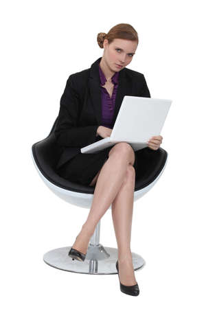 designer chair: Woman sat in designer chair with laptop