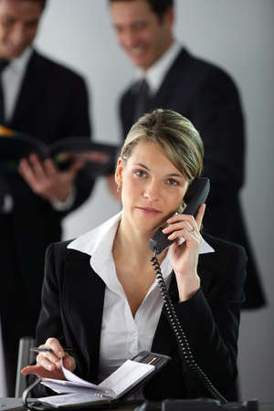 Blond businesswoman making call whilst colleagues are in the background photo