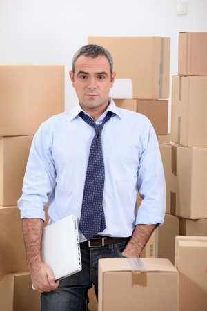 Man in storage depot surrounded by boxes photo