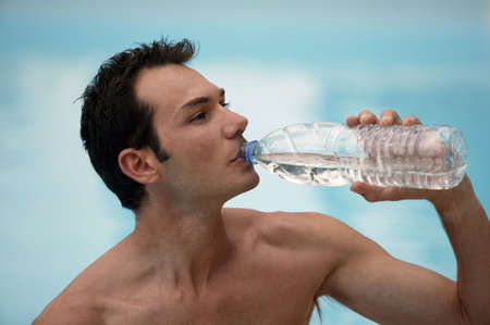Shirtless man drinking from water bottle photo