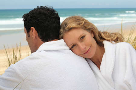 dressing gowns: A man and a woman wearing dressing gowns on a beach