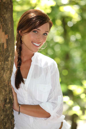 bashful: Woman peeking out from behind a tree Stock Photo