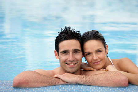 Couple stood together in swimming pool photo