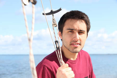 young man on sailing boat offshore photo