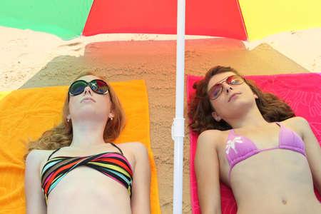 Teenage girls lying on the beach Stock Photo - 12763379