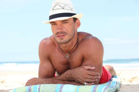 nackte brust: Man liegt am Strand in einem Strohhut Lizenzfreie Bilder