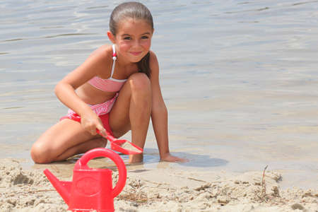 swimming costumes: little girl digging on the beach Stock Photo