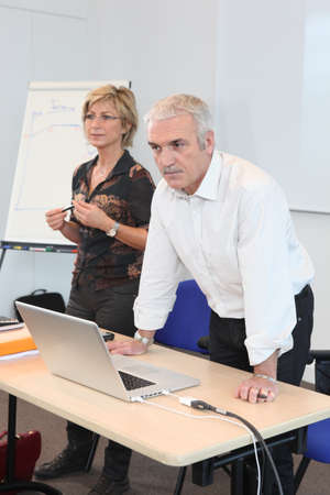 55 60 years: Teacher in classroom with assistant Stock Photo