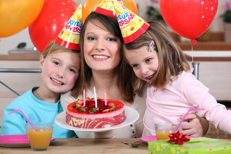cone cake cone: Woman celebrating a birthday with her kids Stock Photo
