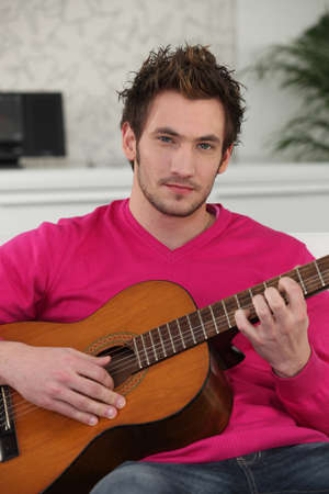 Young man playing a guitar photo