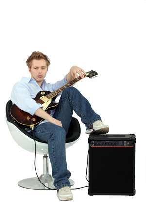 facing to camera: Boy in armchair with guitar and amp Stock Photo