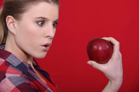 Shocked woman holding apple photo