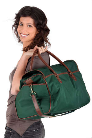Woman carrying a weekend bag over her shoulder photo