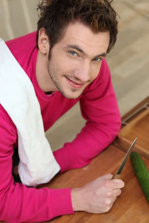 Man cutting cucumber on the countertop Stock Photo - 12762609